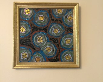 Colorful concentric circle design mosaic in square gold frame