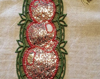 Embroidered lace bookmark apples stacked on book