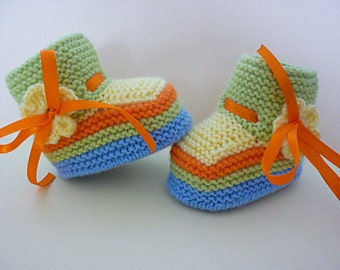 Colorful knitted baby booties/slippers/shoes with a flower and a ribbon