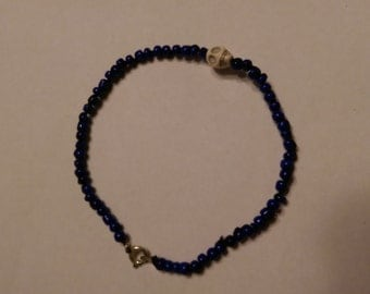 Blue beaded anklet with white skull charm
