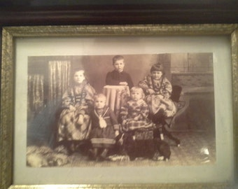 Old photo of kids in wooden frame, looks like early 19th century clothes, with glass