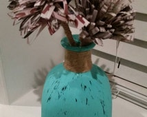 Distressed patron bottle with newspaper flowers