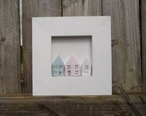 Original framed clay wall art, three tiny houses, blue white and pink in a white wooden frame.