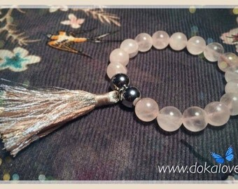 Stretch bracelet made with rose quartz, silver hematite and silver, featuring a pale pink and silver tassel