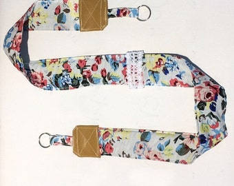 Strap of fabric to blue flowers and leather camera