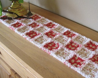 """Winter holiday table runner. Rag quilted. Alternating red and off-white squares featuring whimsical reindeer. 32"""" x 9.5""""."""
