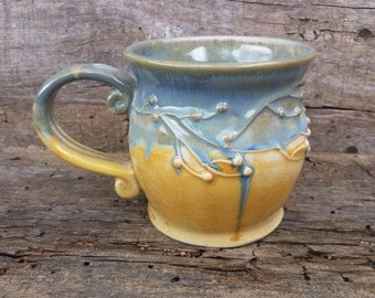 Yellow blue mug with branches and berries