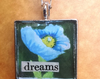 Dreams postage stamp and newsprint collage pendant