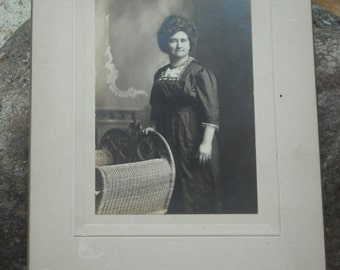 vintage parlor photo of older woman standing with her hand on a wicker chair - Kellogg Studio, Cuba, NY