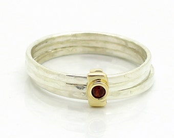Stacking ring with a garnet set in gold & hammered silver
