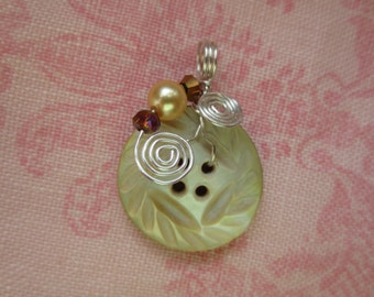 Beautiful vintage silver plated wire wrap carved mother of pearl button pendent. Lot of 1 pendent.