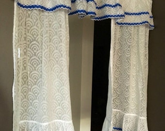 Patterned white sheers with ruffle and bright blue trim, attached valance with ruffled side panels, bathroom or bedroom single window retro