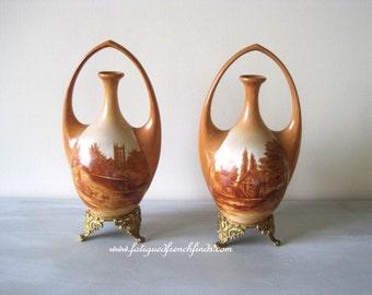 Gebrüder Heubach Schultz Vases on Gilt Metal Mounts Painted in Ochre Shades Bucolic Scenes A Pair of Antique German Ornate Vases