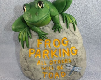 Green Spotted Toad sitting on top of a Frog Parking Sign all others will be Toad