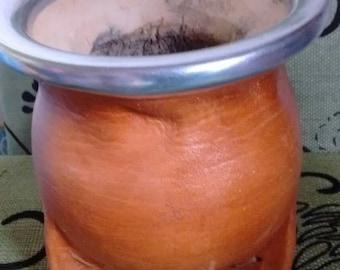 Mate gourd cup with alpaca metal rim a sample of 100 gr of yerba mate tea .