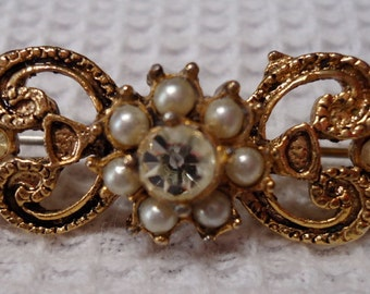 """Gold toned  brooch, vintage, faux diamonds and pearls, ornate open work setting, 2"""" X 0.5"""" .Hinged pin with safety clasp. VFM/MISC/12.1-8.9."""