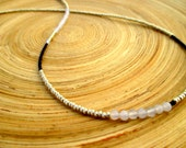 Simple modern beaded necklace with silver and blue seed beads and blue chalcedony