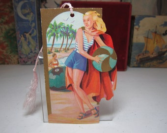 Art Deco 1930's die cut gold gilded American Bridge League bridge tally showing pretty lady in swimsuit on the beach holds beach ball