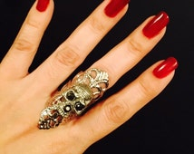 Skull ring made in dull silver color filigree metal, adorned with a small skull on top with crystal eyes, its sizable.