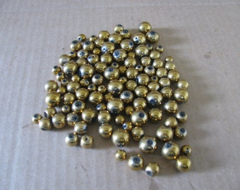 Over 50 gold colored glass beads