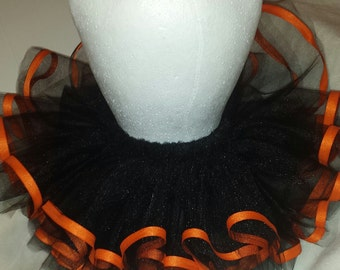 Black tulle with orange ribbon trim tutu. Great addition to a motorcycle outfit or theme.