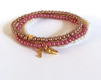 Set of glass pearl stackable bracelets with gold plated charms, cream, mocha and rose pink