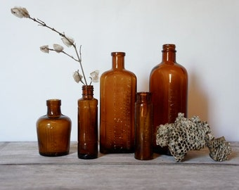 Collection of five amber glass chemist | remedy | poison bottles
