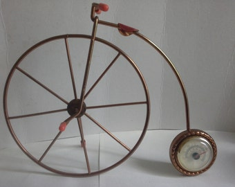 Copper coloured Penny Farthing bike with barometer.
