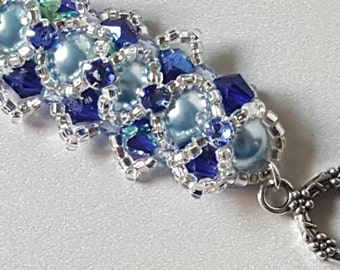 Bracelet of 8mm light blue Swarovski Crystal pearls with 6mm cobalt bicones and criss-crossed amid blue crystal beads by silver seed beads