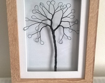 Twisted copper wire tree in a wooden picture frame.