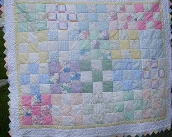 Nine patch hand quilted baby quilt in pastel colors with white and yellow borders