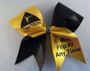 """Gold and Black """"Caution I May Flip At Anytime"""" Cheer Bow w/ Black Rhinestone Center"""