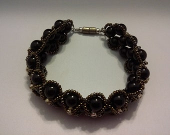 It's a flat black Spiral bracelet decorated with brown Seed Bead.
