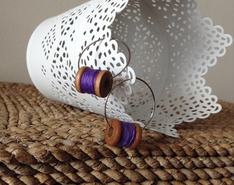 Hanging on by a thread wooden spool with purple thread silver hoop earrings.