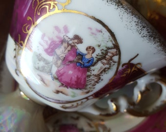 elegant tea cup and saucer,lusterware,porcelain,a victorian courting couple,trimmed,burgundy,gold,fluted,pedestal base,and matching saucer