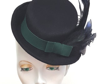 Toy tilt percher hat in hand blocked black wool felt with green trim and green / black feathers - one size elastic fixing