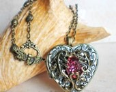 Music box locket, heart shaped locket with music box inside, in bronze with a pink glass jewel and filigree accents.