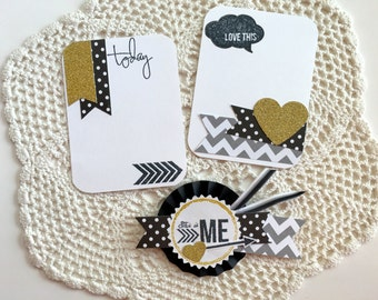 Scrapbook embellishments with rosette and journaling cards in black, white gray and gold