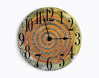 Blue green wall clock with rust swirl middle and black speckles. Circle design.