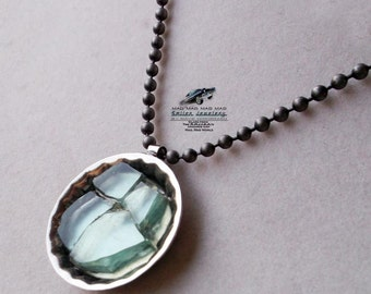 "Aqua  ""bottlecap"" necklace made with ""It's a Mad, Mad, Mad, Mad World"" car glass."