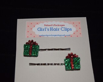 Green present with red bow hair clips/barrettes/bobby pins