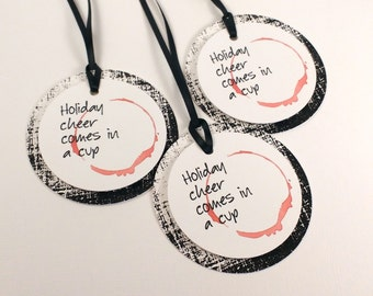 Holiday Cheer comes in a Cup- Wine tag with distressed background- Spilled Wine red with Black Ribbon
