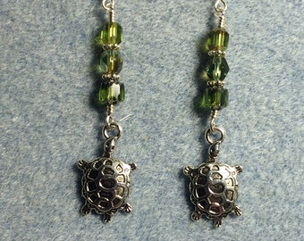 Silver turtle charm earrings adorned with olive green Czech glass beads.