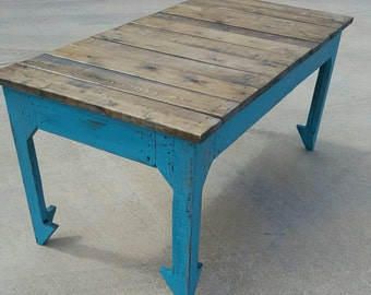 Boho style, reclaimed wood coffee table with split arrow legs and stained top, finished in honey maple stain and distressed turquoise finish