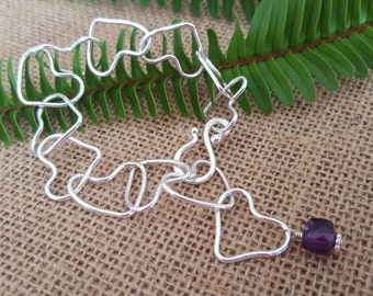 Interlocking fine silver heart bracelet finished with amethyst cube. 999 silver hearts.