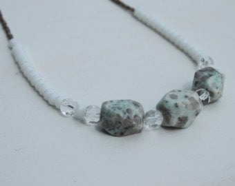 White with light greeny blue and grey flecked granite with white and silver glass beads