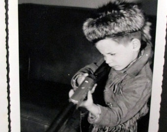Young boy in his Daniel Boone outfit with coonskin hat aming  bb gun 1950's