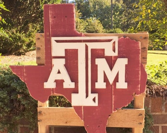 Maroon state of Texas wood pallet sign with a white Texas A&M logo in the center.