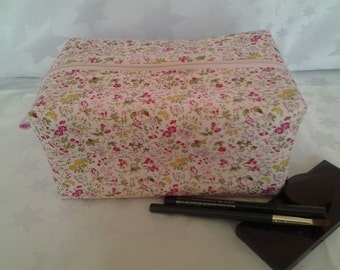 Oblong makeup / toiletries bag in a ditsy floral pink and green fabric.