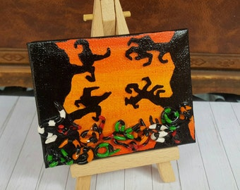 Small canvas in black/orange on easel with haunted forest and Creepers